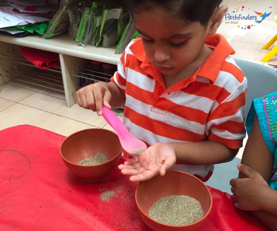 a child is observing a sand